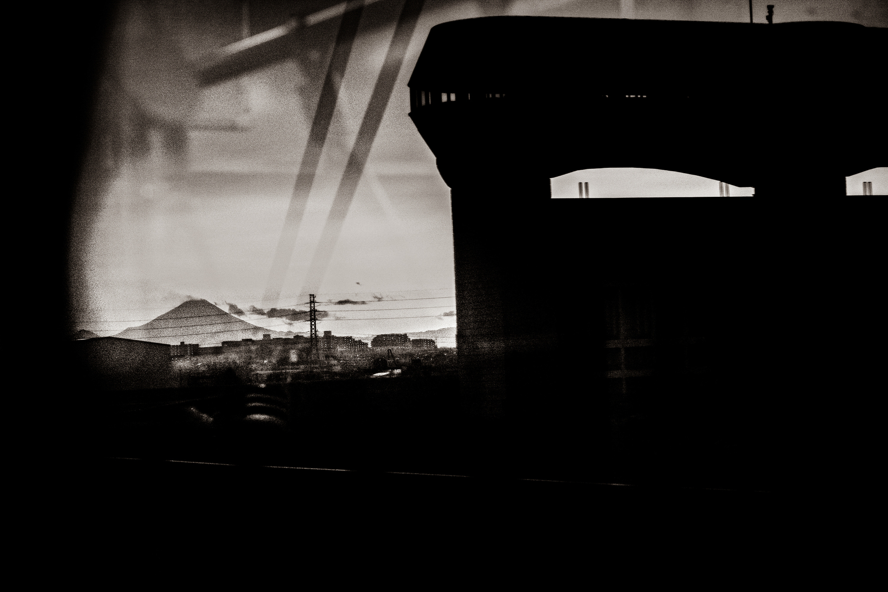 Mt Fuji and a flood control gate, as seen from an elevated train